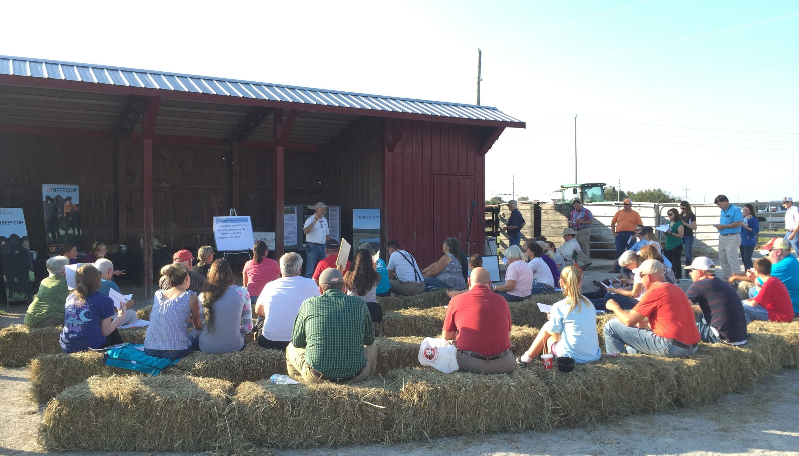 people sitting on hay bales while listening to someone talk
