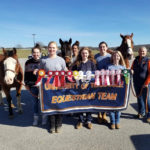 Equestrian team members posing with ribbons and horses